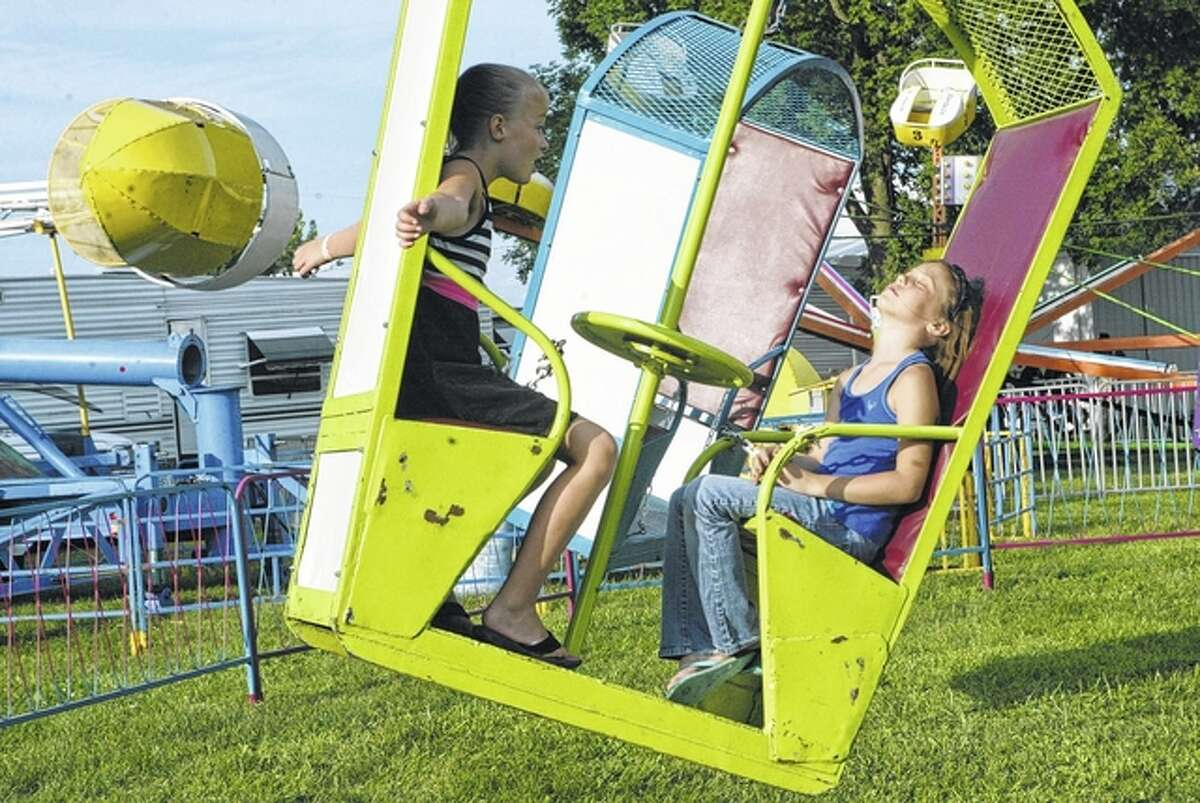 Children spin in multiple directions Tuesday on a carnival ride at the Brown County Fair in Mount Sterling. The fair began Tuesday evening and runs through Sunday.