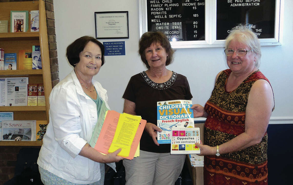 Kathy English (from left) holds math cards while Pat Kinsell of the Morgan County Health Department and Martha Hauck show some of the French books being donated.