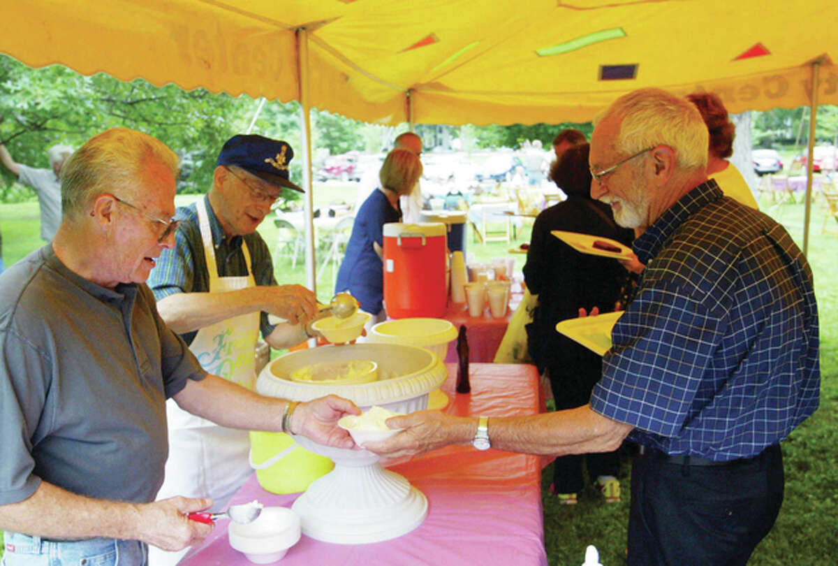 Sons of the American Revolution members Richard Cook (left) and Bob Dalton serve ice cream last year during the annual Duncan Mansion ice cream social on the lawn of the 170-year-old house in Jacksonville. The mansion is one of a few places that has served as the official Governor's Mansion outside of Springfield when Joseph Duncan was governor from 1834 to 1838. Proceeds of the ice cream social go toward preserving the local landmark.