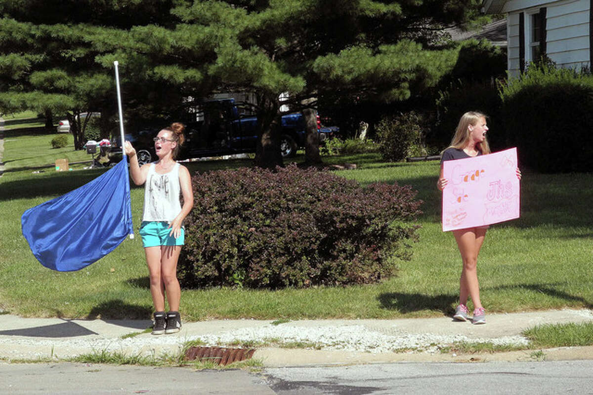 David Blanchette   Journal-Courier Serenity Norman (left), 15, and Brandy Maddox, 14, promote a nearby garage sale from the corner of Westgate Avenue and Westfair Drive on Friday in Jacksonville.