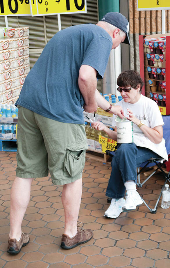A kind Samaritan donates some money to Karen Galyen on Saturday morning at the Godfrey Schnuck's store in support of the Madison County Association of the Blind An organization of blind people, for blind people.