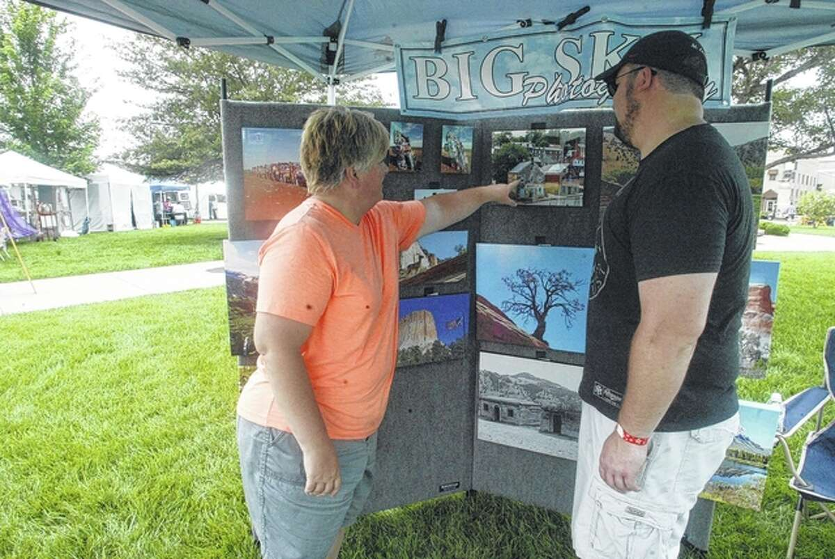 Jennifer Curtis (left) of Woodson, owner of Big Sky Photography, talks Saturday with Shawn Artis of South Jacksonville during Jacksonville Main Street's fifth annual Art Fair on the Square.