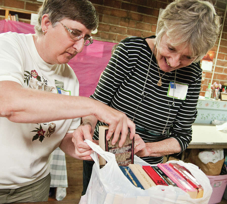 Jane Zimmerman, left, was learning Irene Gulovsen strategies on stuffing as many books into a grocery bag as possible — the cost for each bag, just $3.