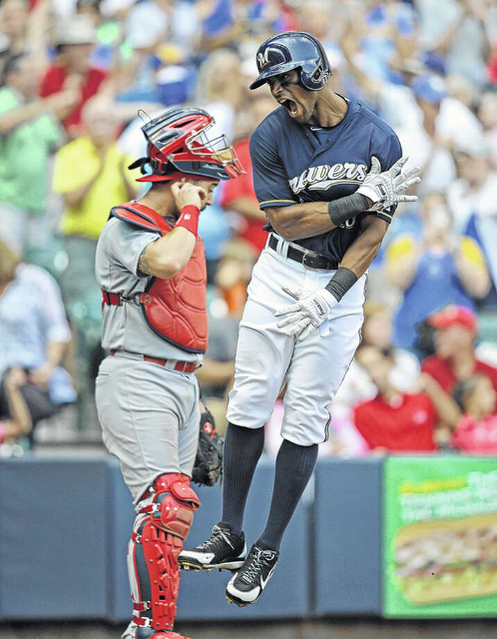 The Brewers' Khris Davis (right) crosses the plate after his two-run home run while Cardinals catcher Tony Cruz looks on in the eighth inning Sunday in Milwaukee. Photo: Associated Press