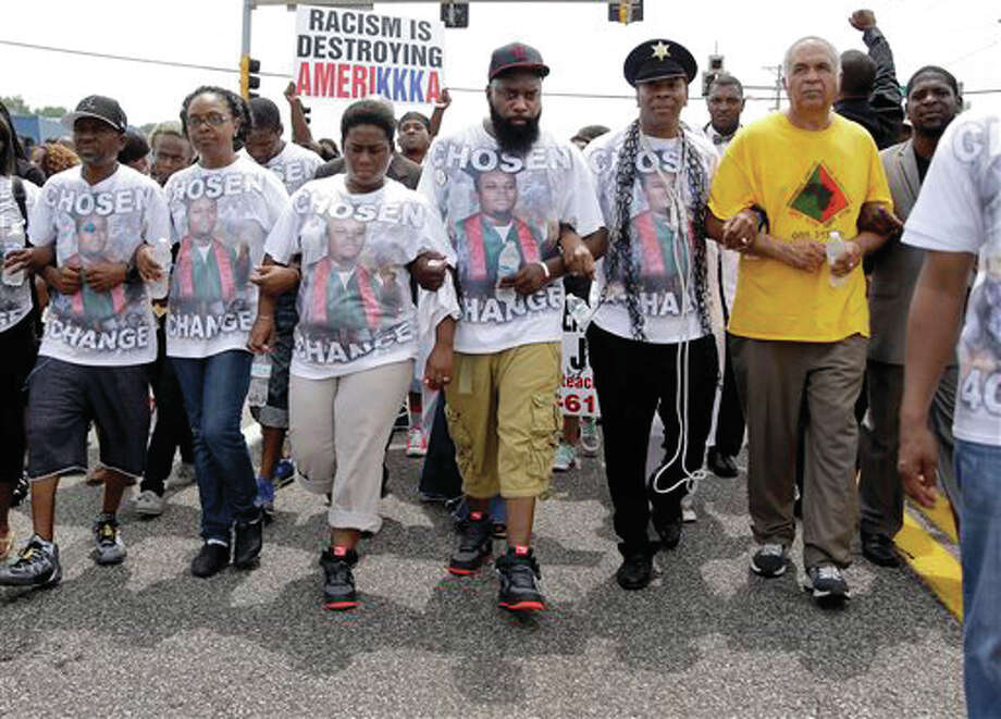 Michael Brown Sr., center, takes part in a march in remembrance of his son, Michael Brown, Sunday, Aug. 9, in Ferguson, Mo. Sunday marked one year since Michael Brown was shot and killed by Ferguson police officer Darren Wilson. Photo: AP Photo/Jeff Roberson