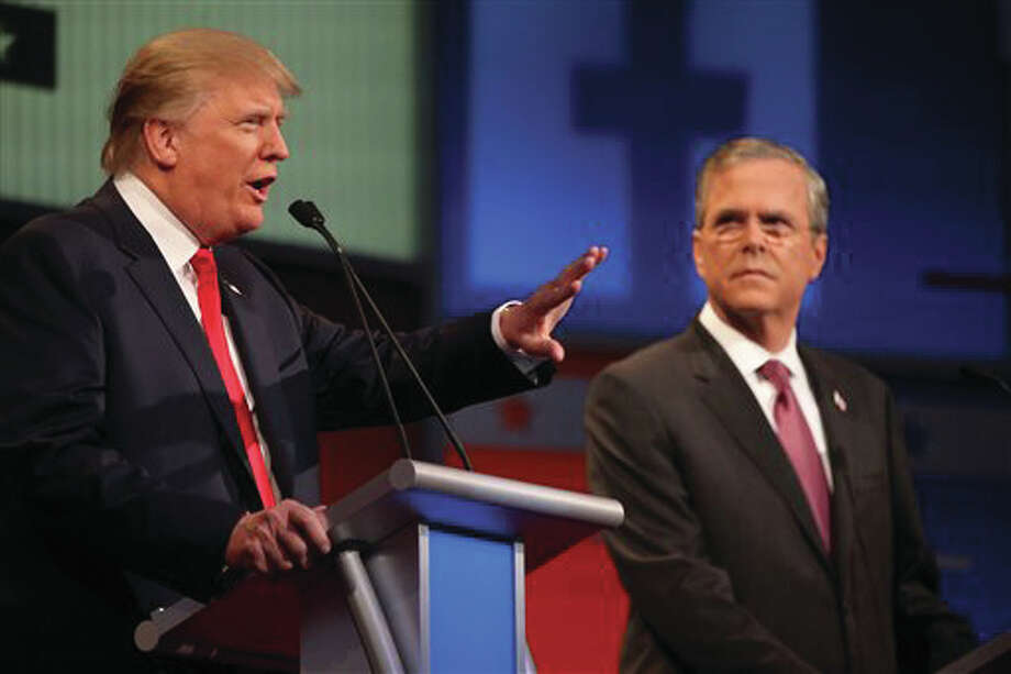 Republican presidential candidate Donald Trump, left, speaks as Jeb Bush listens during the first Republican presidential debate at the Quicken Loans Arena Thursday, Aug. 6, 2015, in Cleveland. Photo: AP Photo/Andrew Harnik