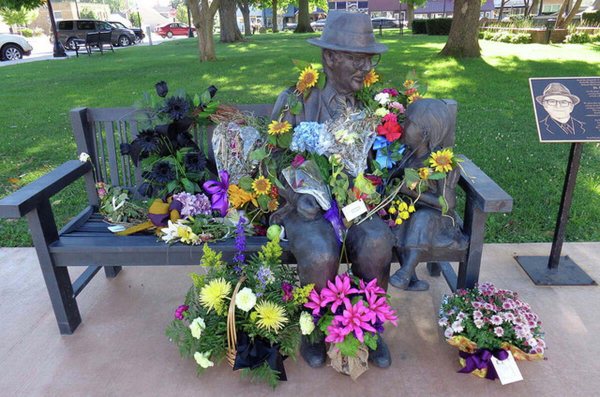 A statue of Dr. Russell Dohner in the Rushville Central Park Square is filled with flowers in memory of the longtime country doctor. Dohner, who died Friday at age 90, practiced medicine in the Rushville area for 58 years. He continued making house calls and never charged more than $5 for a visit until his retirement in 2013. He was buried Tuesday.
