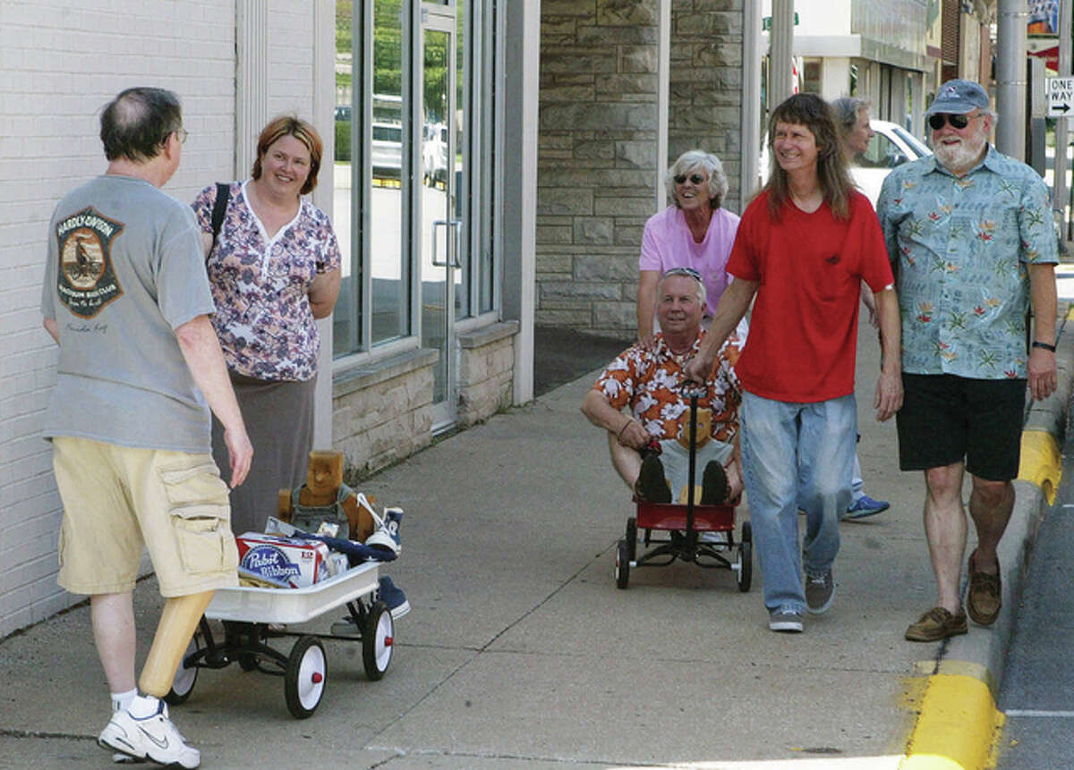 """Ross Green (left) pulls a red wagon painted white in memory of his friend, Richard """"Dick"""" Vorhes. Others who were friends of Vorhes joined in on what would have been his 65th birthday."""