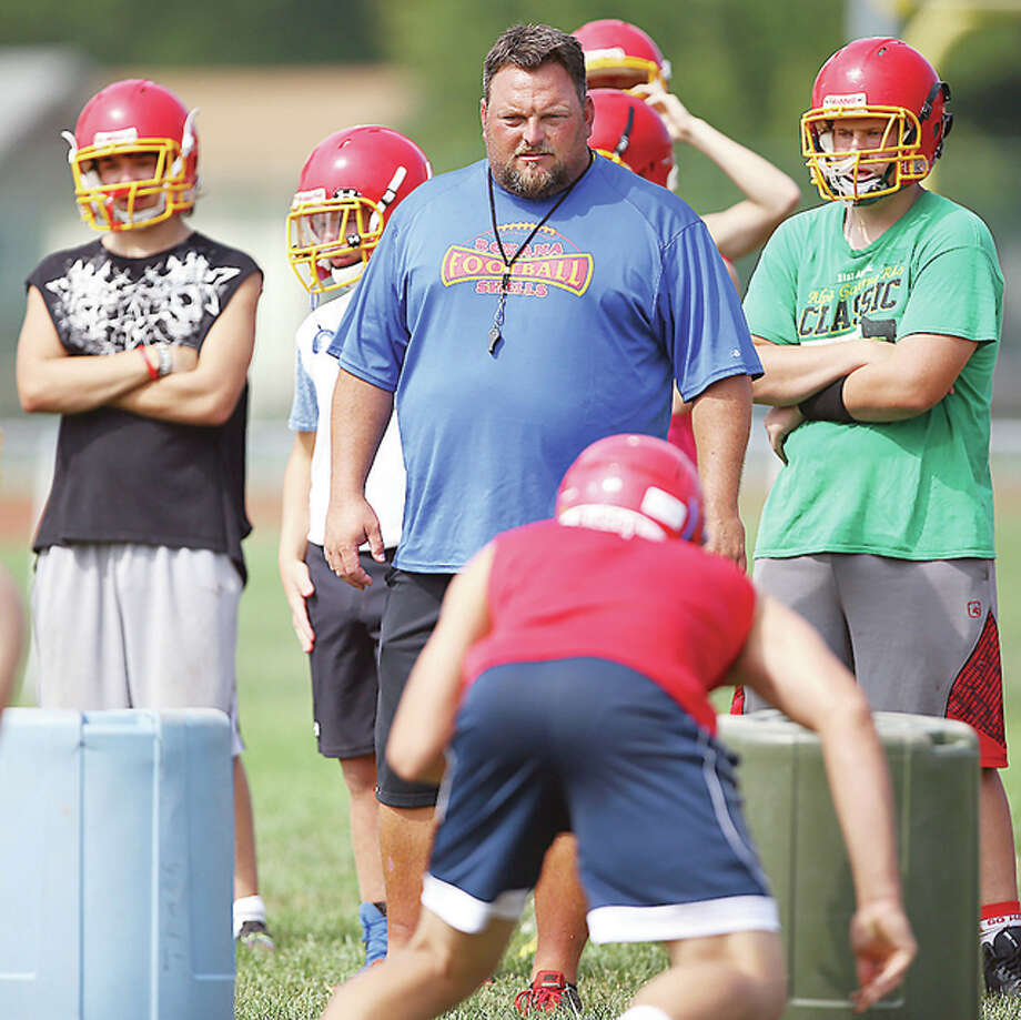 Roxana Shells head coach Pat Keith watches as his team goes through drills during the first day of football practice on Monday. The Illinois High School Association limits will not allow full-contact practices until Saturday. In the meantime, the Shells are improvising with upside-down trash cans to simulate opposing linemen during non-contact drills. Photo: Billy Hurst | For The Telegraph