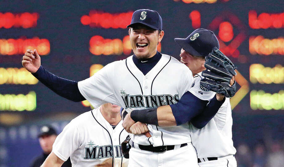 Seattle Mariners pitcher Hisashi Iwakuma is hugged by first baseman Logan Morrison, right, after the final out of Iwakuma's no-hitter against the Baltimore Orioles Wednesday in Seattle. Photo: AP