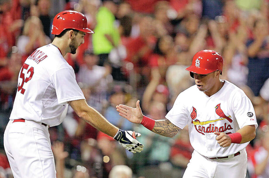 The Cardinals' Kolten Wong, right, celebrates with teammate Michael Wacha after they both scored on a fielder's choice off the bat of Jason Heyward in the third ining of Wednesday's 4-2 win over Pittsburgh at Busch Stadium. Photo: AP
