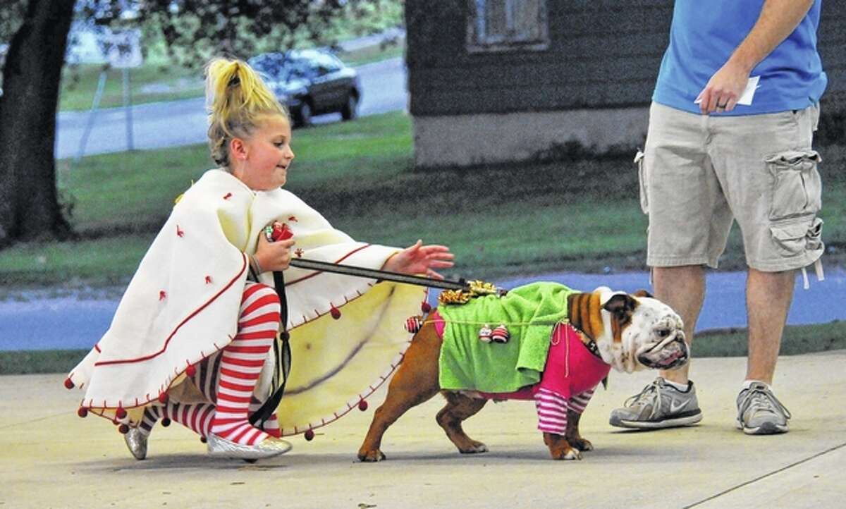 Toby Layne Behrends and Maggie, dressed as Christmas ornaments, make their way through the crowd at the Chandlerville Burgoo. This is the second year for Chandlerville Burgoo's Bark in the Park costume contest. Toby won best costume last year and won grand champion overall Thursday and received the grand prize of $50. This is Chandlerville Burgoo's 68th annual celebration. It continues today.