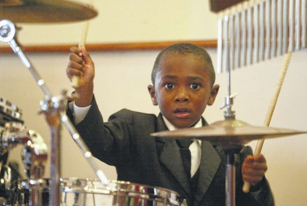 """Three-year-old James """"J.D."""" Davis III of Springfield shows off his drumming skills Saturday at the """"Youth on the Move for God"""" worship service at Community Temple Church of God in Christ in Jacksonville."""
