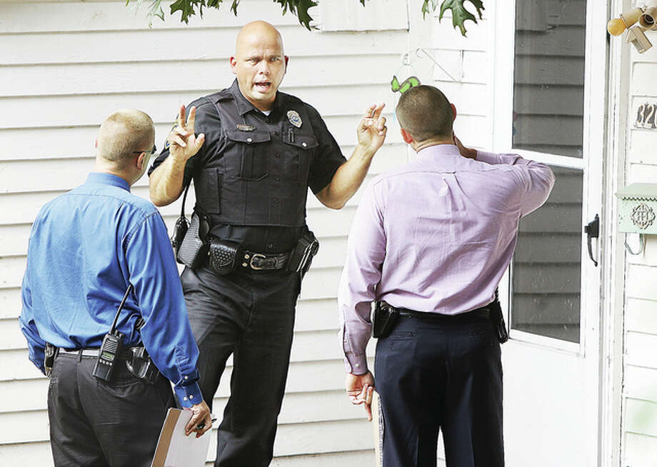 Alton Police Sgt. Seth Stinnett, center, explains events to two Alton detectives Tuesday before they enter the house in the 3200 block of Oakwood in Alton where police responded to a 911 call to discover a 6-month old boy who had reportedly been dead for several hours. Alton police declined to comment on the death Tuesday, which is under investigation.