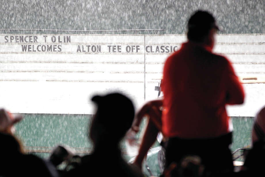 Golfers, coaches and spectators seek shelter and wait out a lengthy rain delay Tuesday during the Alton Tee Off Classic at Spencer T. Olin Golf Course in Alton. The 21-team classic was eventually cancelled. It wiull not be rescheduled.