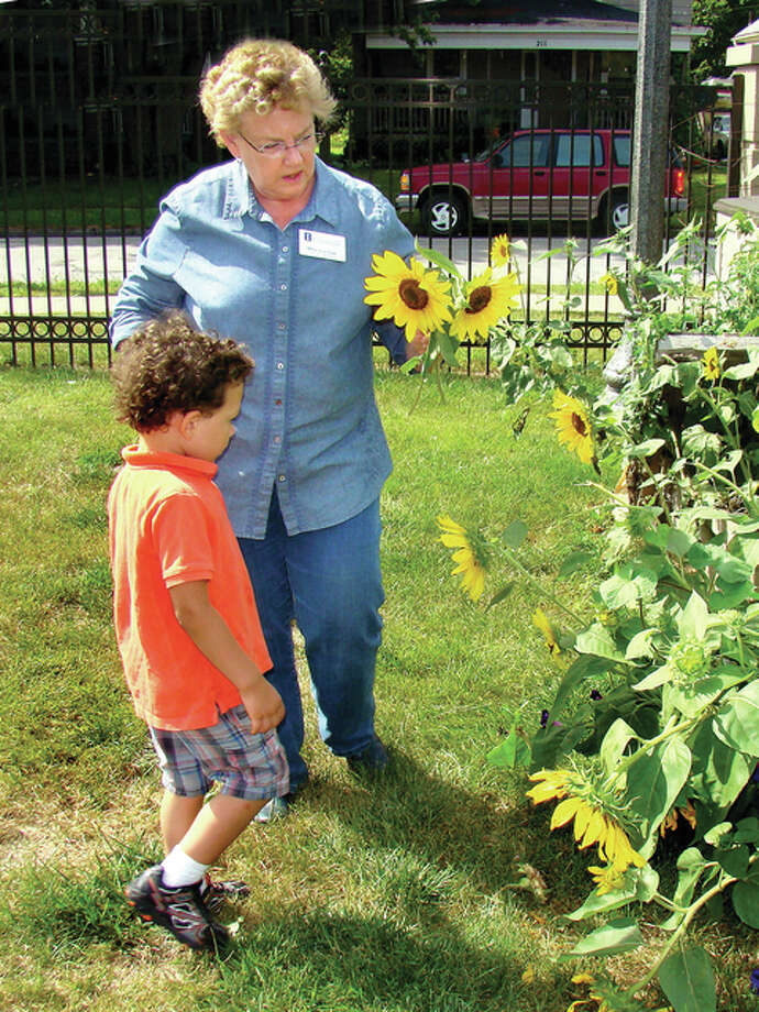 Roger Deem | Journal-Courier Mary Lou Lael picks sunflowers with the help of a young gardener.