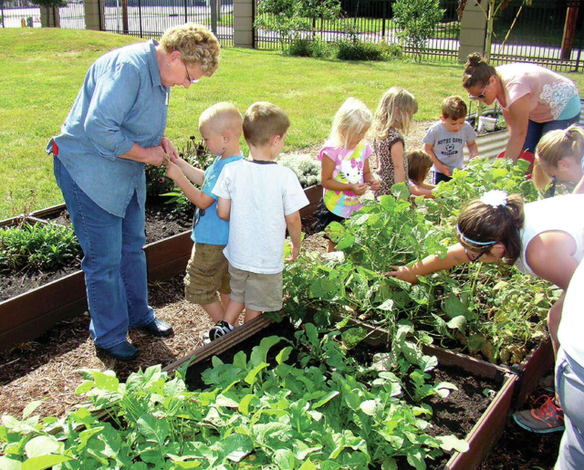 Roger Deem   Journal-Courier Children and volunteers tend to the garden behind the Jacksonville Public Library.