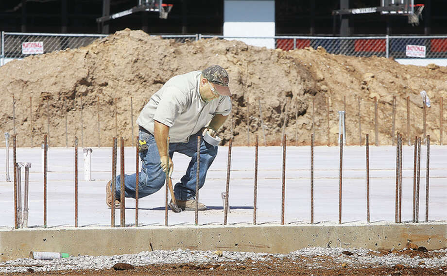 A worker seals off utilities coming through the concrete slab for the new Early Childhood Center addition behind South Roxana Elementary School Thursday. The Roxana district also received $50,000 Thursday from Shell Oil Company to convert the former cafeteria at the high school into a multi-purpose student center.