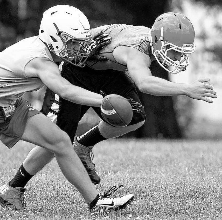 A Jacksonville defender bats away a pass during a 7-on-7 at Illinois College earlier this summer. Photo: Dennis Mathes | Journal-Courier