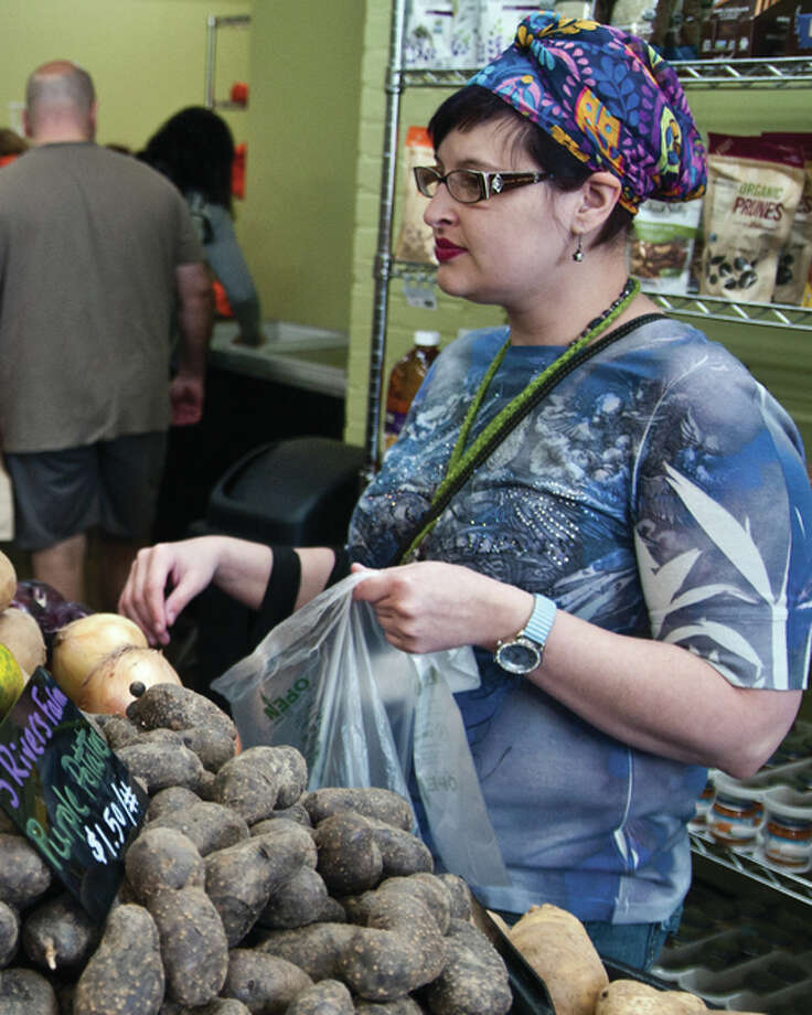 Danielle Baker added a variety of vegetables to her bag; the produce was harvested by local farmers.