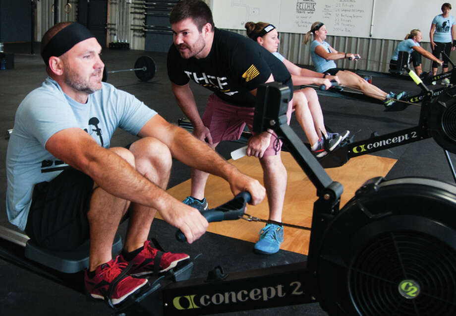 Corey Waltz coaches Jason Arrowsmith in the 1974 meter row Saturday morning inside the Iron House Crossfit facility in Godfrey. It was Waltz's idea to commemorate the late Cpl. Chris Belchik and worked with Chris's brother, Brian, a member at Iron House Crossfit. The significance to 1974 is the year that Chris was born. Photo: Dan Cruz | For The Telegraph