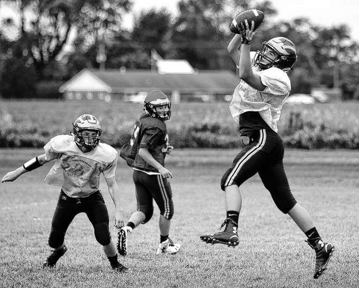 A Rushville-Industry player leaps to catch a pass during a recent practice.