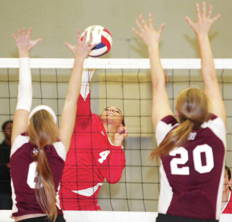 Alton's Savannah Fishcer (middle) tries to split a pair of Belleville West blockers with an attack during a SWC match last season at Alton High in Godfrey. Fisher is back for her junior season with the Redbirds, who open their season Monday night at home against the Columbia Eagles. Photo: James B. Ritter / For The Telegraph