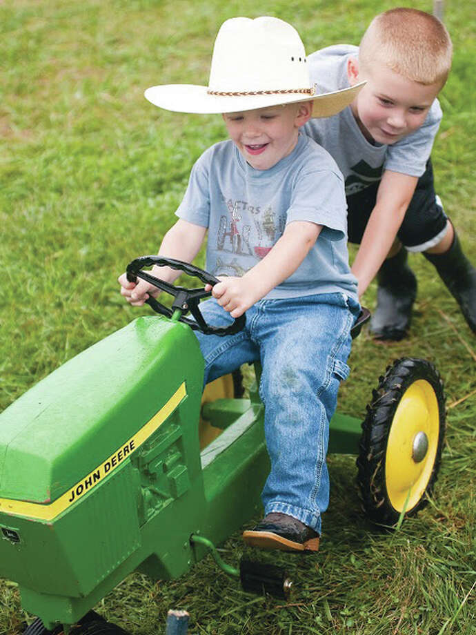 Joshua Cordes, 5, pushes his younger brother, James, on a miniature John Deere tractor Sunday at the silver anniversary of the Tri-County Antique Club's Olden Days Festival in Dow. Photo: Dan Cruz | For The Telegraph