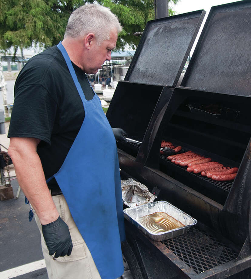 Chemist-by-day Bill Stork, who is a professional BBQ chef and owner of Riverbend-based Black Iron BBQ, enticed people with his brats, pulled pork, brisket and hot dogs Saturday night at the Alton Marina during its free 19th anniversary party. Photo: Dan Cruz | For The Telegraph