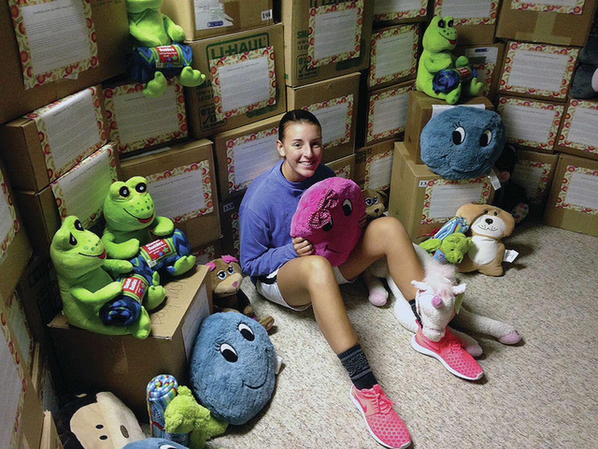 Madi Allen, 17, of Jacksonville is surrounded by 35 boxes of toys, blankets and other items that she donated in July to Children's Hospital in St. Louis. Allen was hospitalized in St. Louis for nearly two months when she was 12 years old after she became ill with what was later diagnosed as Influenza B and Methicillin-resistant Staphylococcus aureus.