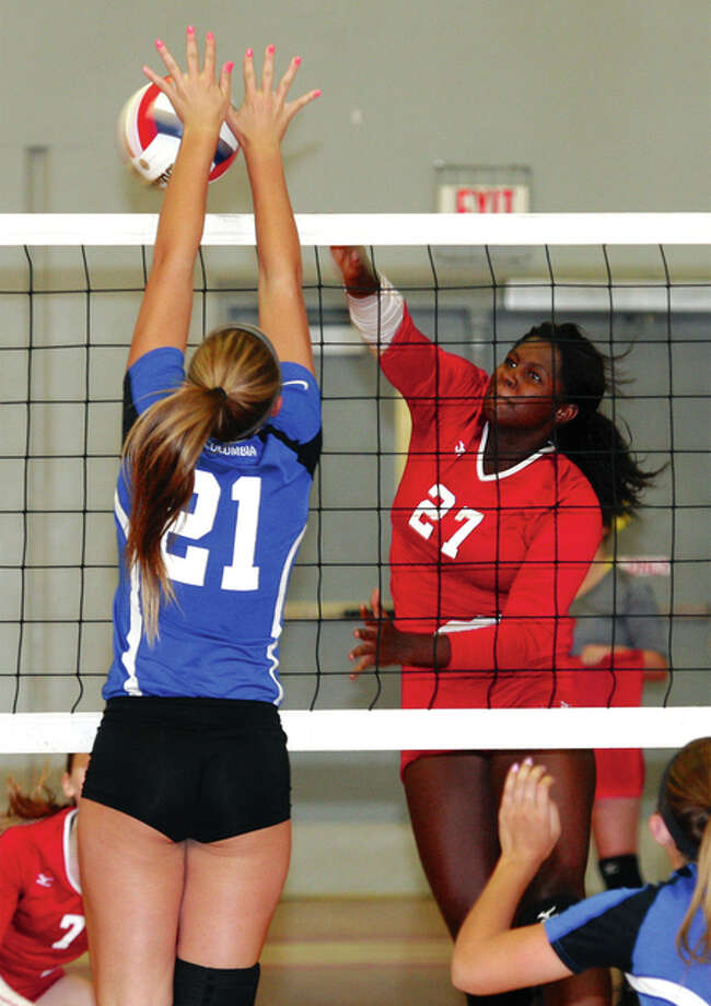 Alton's Jada Green (right) goes cross court for a kill while Columbia's Claire Foster goes up for the block in the volleyball season opener for both teams Monday at Alton High in Godfrey. Photo: James B. Ritter / For The Telegraph
