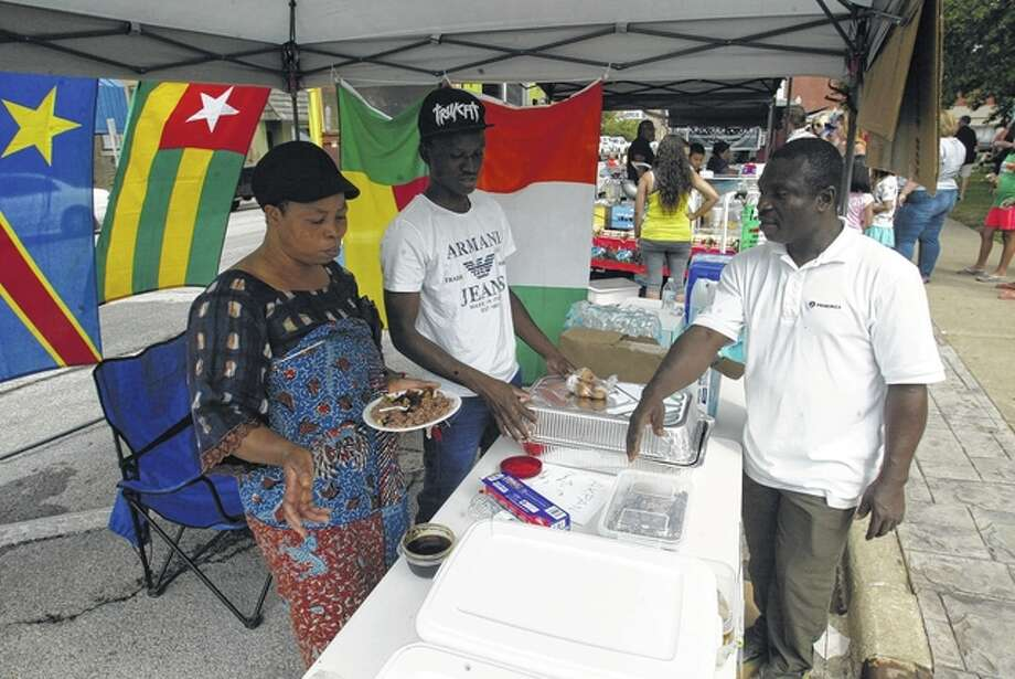 Members of Beardstown's African community had a food stand at Saturday's Taste of Beardstown on the Beardstown square. From left are Kanle Kouevidjin, Sebastian Sow and Sam Komla Ewu. Photo: Greg Olson | Journal-Courier