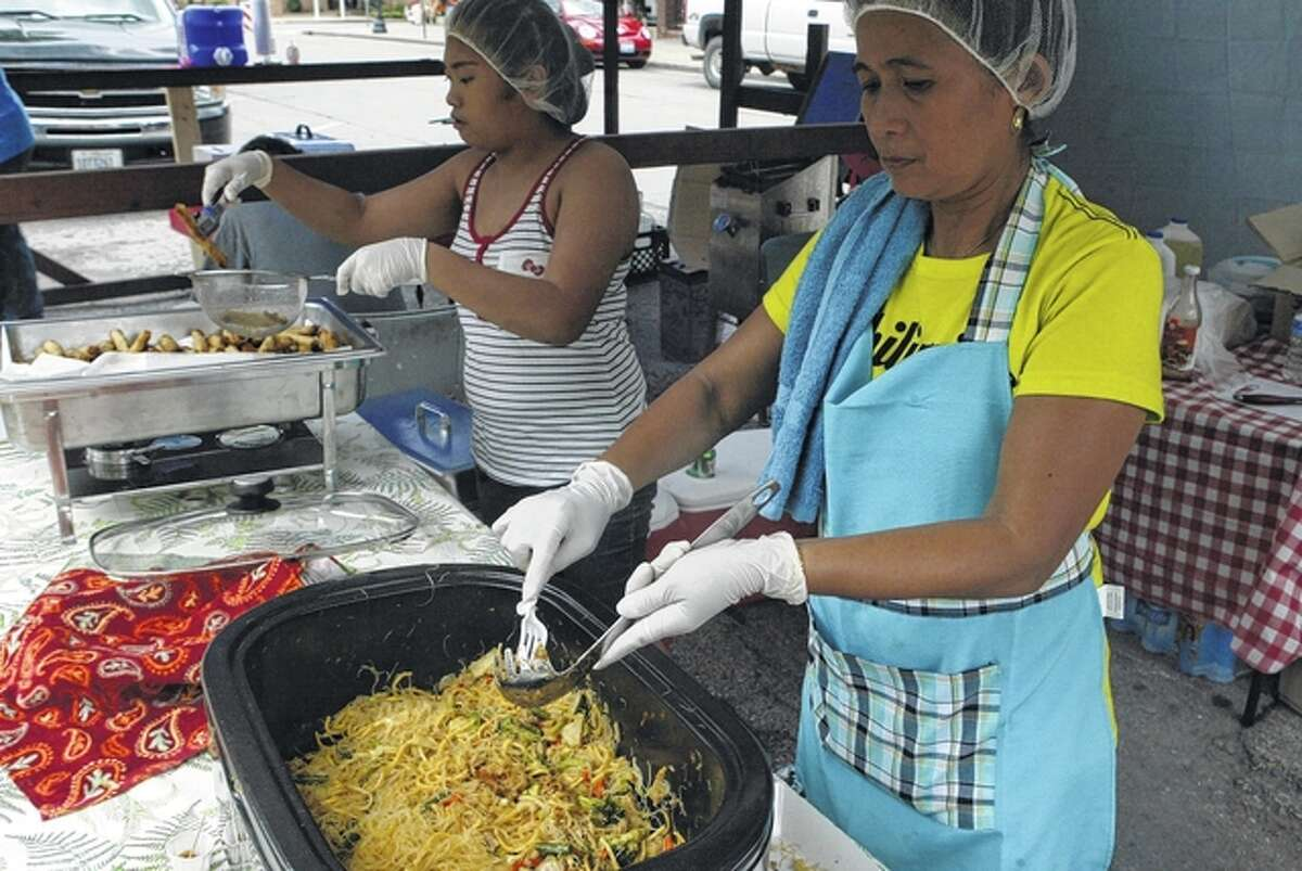 Alizza Demillo (left) and her aunt, Lily Dineros Coats, prepare some Filpino food Saturday at Taste of Beardstown.