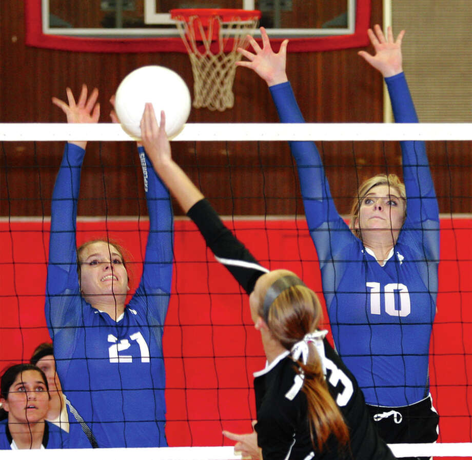 Marquette Catholic's Andria Pace (left) and Michelle Cameron (10) put up a block as Calhoun's Kristen Wieneke extends to get the ball over the net Tuesday night at the Roxana Tournament. Photo: James B. Ritter | For The Telegraph