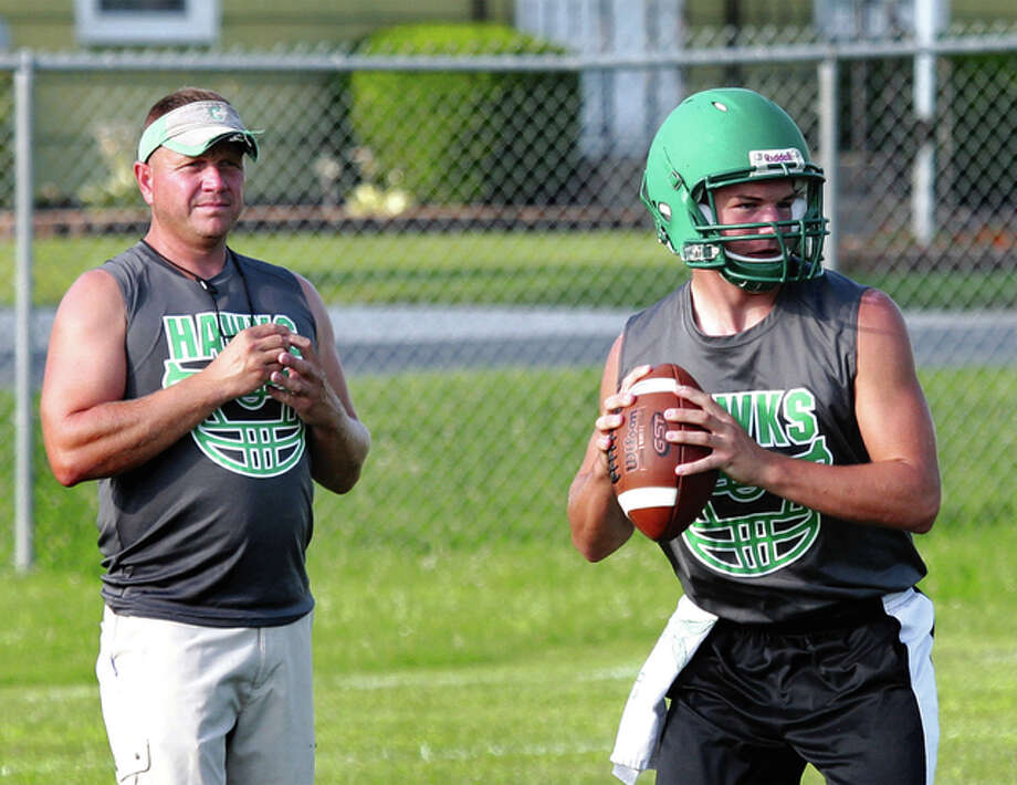 Carrollton quarterback Wade Prough (right) works under the watchful eye of Hawks coach Nick Flowers during a 7-on-7 competition this summer in Jerseyville. Prough is the heir apparent for a quarterback job left vacant with the graduation of Carrollton's career passing leader Jacob Smith. Carrollton finished 13-1 and was the runner-up in Class 1A last season. Photo: Dennis Mathes, Journal-Courier James B. Ritter / For The Telegraph