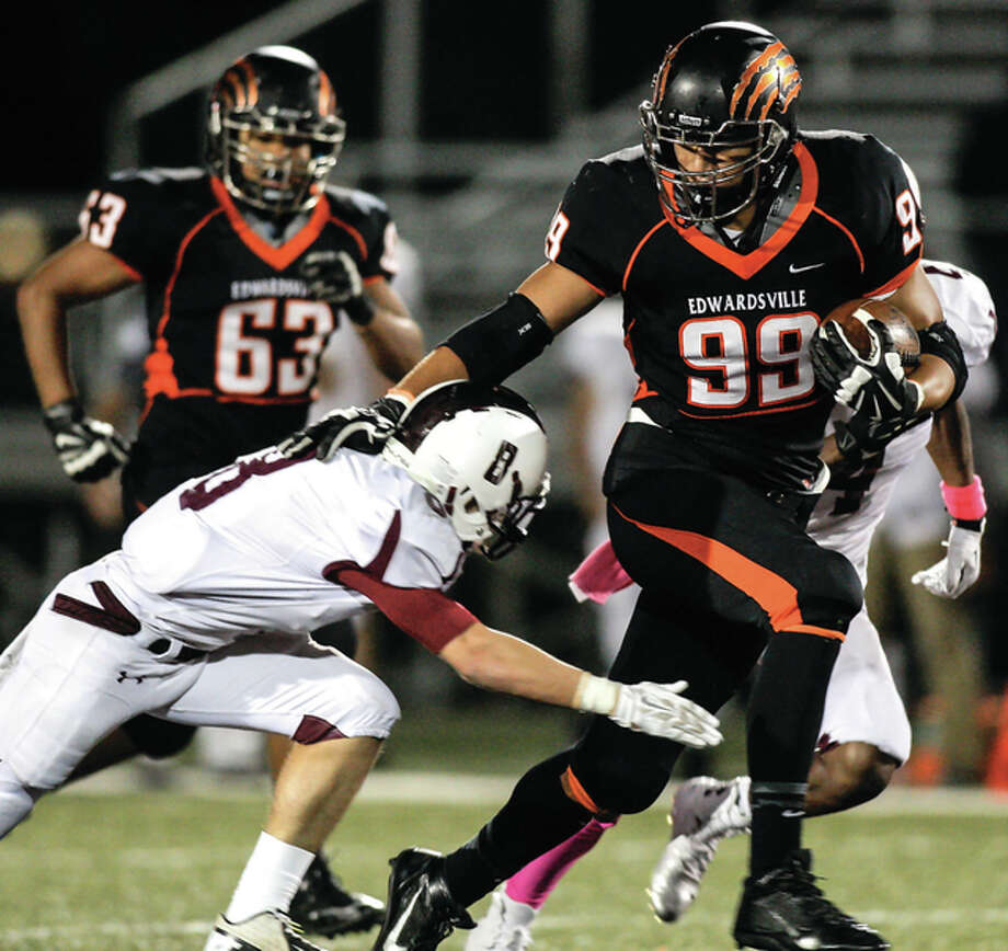 Edwardsville's AJ Epenesa (99) fends off a Belleville West tackler Jones during a game last season in Edwardsville. Photo: Scott Kane | For The Telegraph
