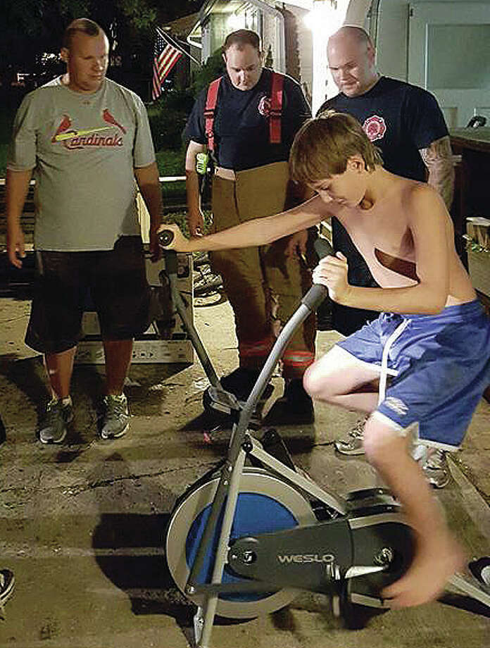 Bethalto firefighters watch 11-year-old autistic boy Shane Laycock enjoy the cycle they assembled for him.