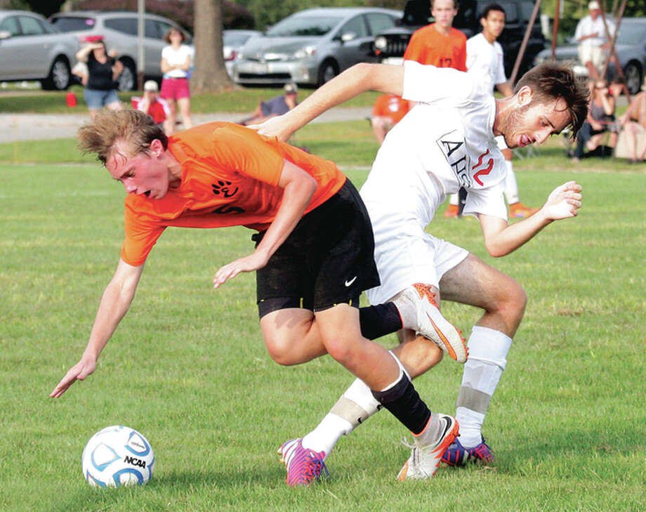 Edwardsville's Jacob Mulvihill gets tangled up with Alton's Carter St. Cin as they battle for the ball Saturday night at Gordon Moore Park in Alton. Photo: James B. Ritter | For The Telegraph