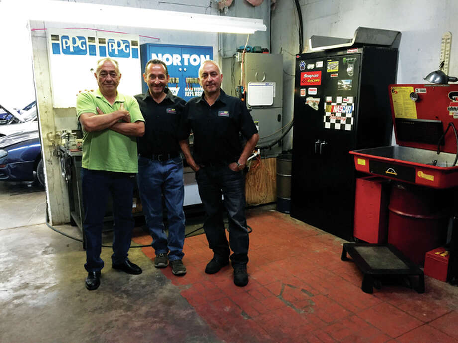 Transcar owners and brothers Ignacio, right, and Edgar Lopez, center, pose in their workshop with elder brother, Roberto.