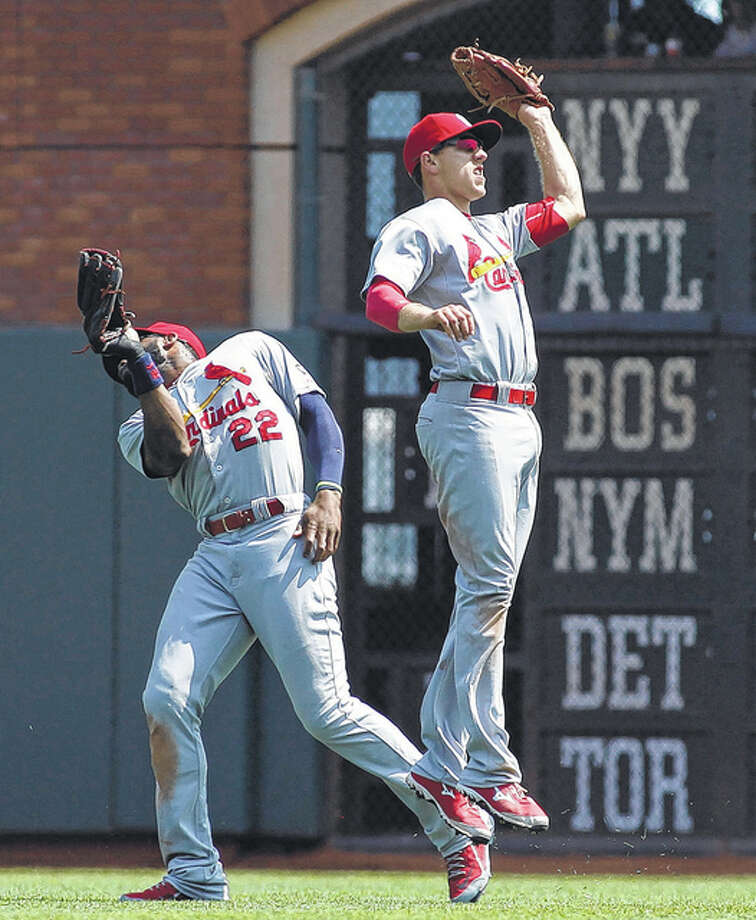 Cardinals center fielder Stephen Piscotty (right) ranges in front of right fielder Jason Heyward to catch a fly ball hit in the third inning against the Giants on Sunday in San Francisco. Photo: Associated Press