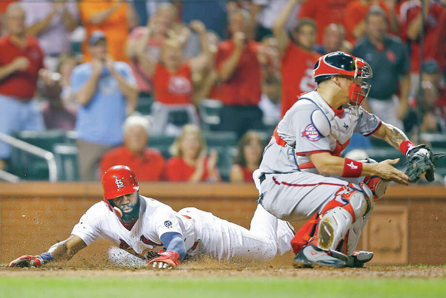 The Cardinals' Jason Heyward, left, slides in safely ahead of the tag by Washington Nationals catcher Jose Lobaton, on a single by Kolten Wong in the seventh inning Monday at Busch Stadium. The Cardinals won the game 8-5. Photo: Billy Hurst | For The Telegraph