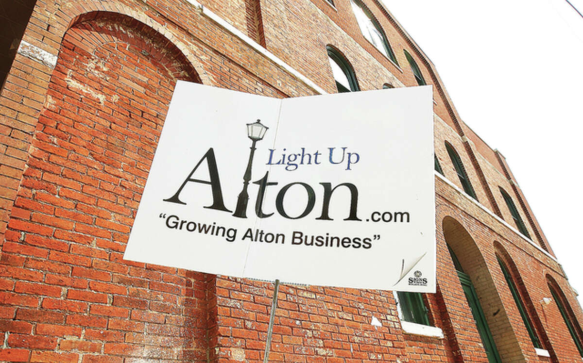 John Badman/The Telegraph A Light Up Alton sign sits in front of a building Tuesday in the 200 block of East Broadway in Alton.