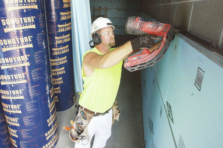 A construction worker nails up strips to hold insulation in place on the interior of the new Advanced Auto Parts store being constructed on Edwardsville Road in Wood River. The new store, which is expected to open in late October, is located next to the Hit n Run store at the corner of Edwardsville Road and 9th Street.