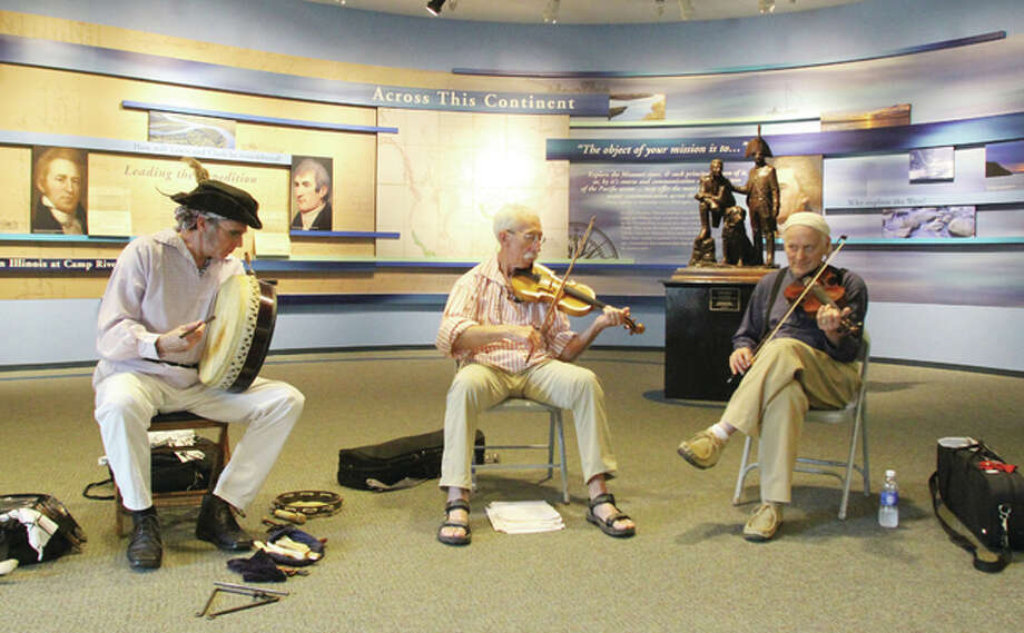 From left, percussionist Scott Miller, and fiddle players Lindell Blackford and Wayne Schell play in the lobby of the Lewis and Clark Historic Site Museum during the site's annual music festival Saturday. The festival included a number of performers playing traditional styles of music.