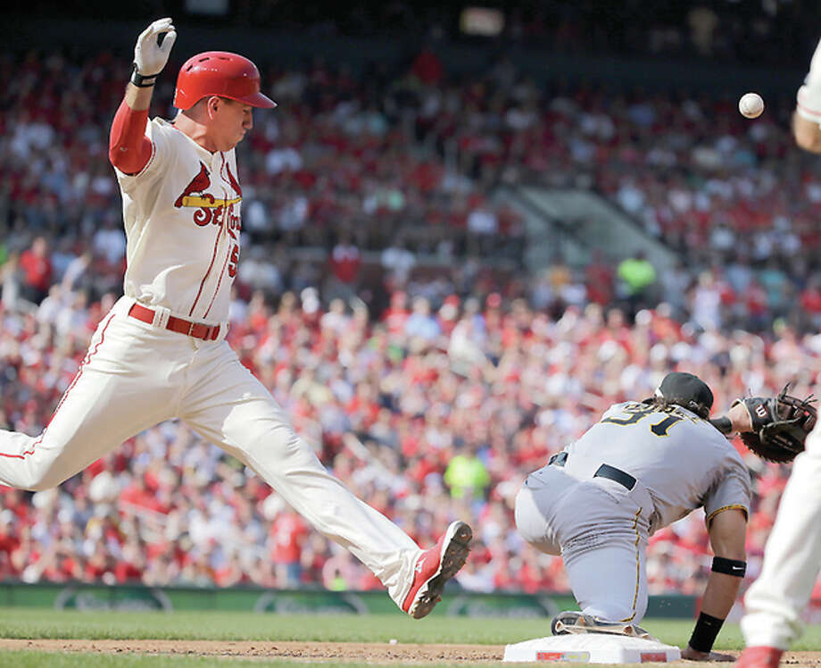 The Cardinals' Stephen Piscotty, left, reaches base as the throw gets away from Pirates first baseman Michael Morse Saturday at Busch Stadium. Two runs were scored and Pirates second baseman Josh Harrison was charged with a throwing error on the play. Photo: Jeff Roberson   AP