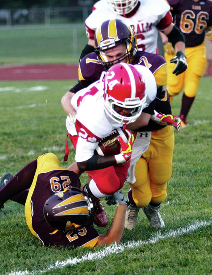 EA-WR's Zaide Wilson (bottom) and Justin Englar (top back) team up to pull down Centralia's Keshawn Marshall during the first quarter of Friday night's nonconference football game at Memorial Stadium in Wood River. Photo: James B. Ritter / For The Telegraph