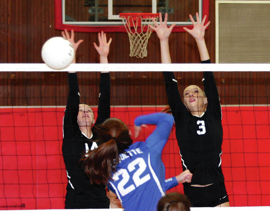 Calhoun's Junie Zirkelbach (left) and Kristen Wieneke (right) put up a block on Marquette Catholic's Caitlyn Hanlon (22) during pool play Aug. 25 in the seventh annual Roxana Tournament in Roxana. Photo: James B. Ritter / For The Telegraph
