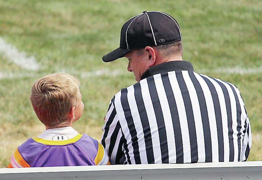An Illinois High School Association football official visits with the son of Monticello coach Cully Welter prior to Saturday's game at Macomb. The photo, by Ann Wildman, was posted on the IHSA website in light of an incident in Texas in which a pair of prep players allegedly leveled intentional hits on an official during a game. Photo: IHSA