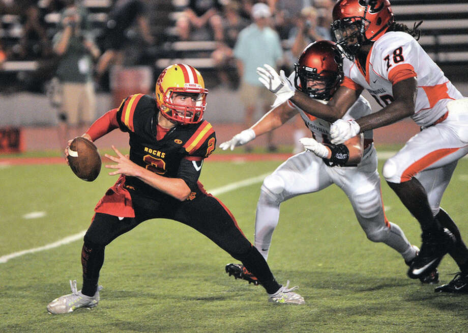 Rock Island quarterback Alek Jacobs (left) cannot scramble away from Edwardsville's Cyress Ahart and Desmond Chapple (right) before being sacked in the Tigers' win last Friday in Rock Island. Photo: Paul Colletti /qconline.com