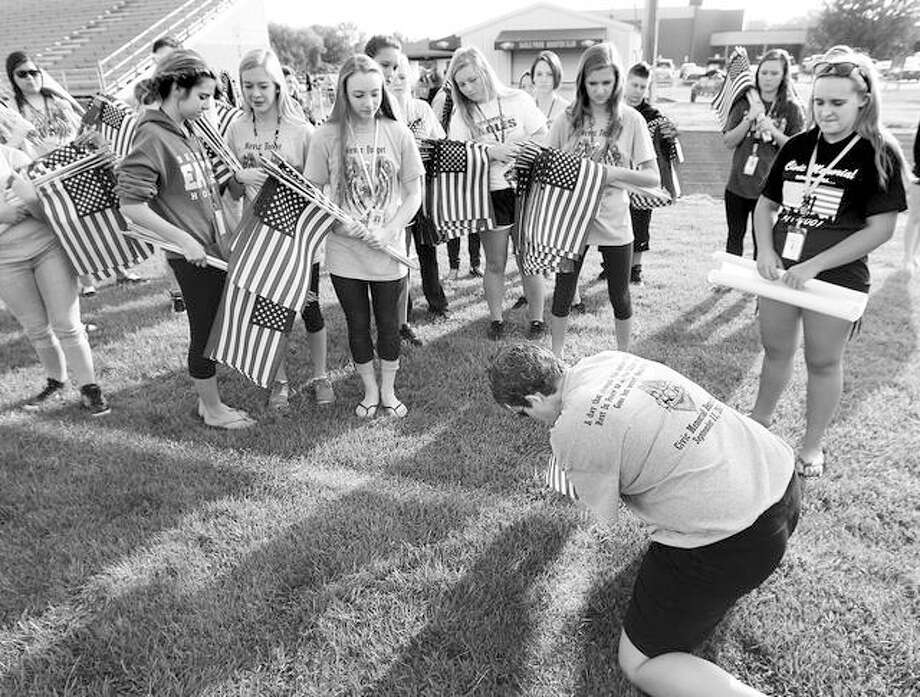 Organizer and physical education teacher Angela Parish from Civic Memorial High School in Bethalto, plants the first of 2,977 flags Thursday morning for the memorial service held to honor those who died in the terrorist attacks on Sept. 11, 2001.